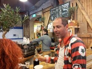 שף ניר צוק מסביר לנו על הקפה, ליד דוכן הקפה בבזאר הקולינארי